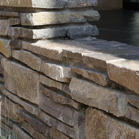 石積のデザインウォールが重厚感を添えるエントランス
