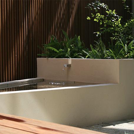 斜めにデザインされたデッキと水盤が奥行きを感じさせるテラス